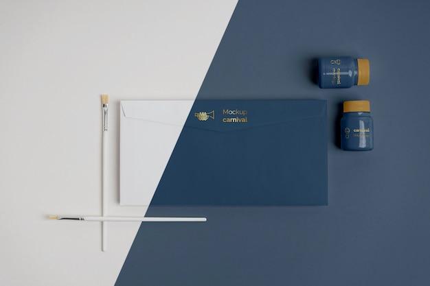 Bovenaanzicht van minimalistische carnaval uitnodiging in envelop met penselen