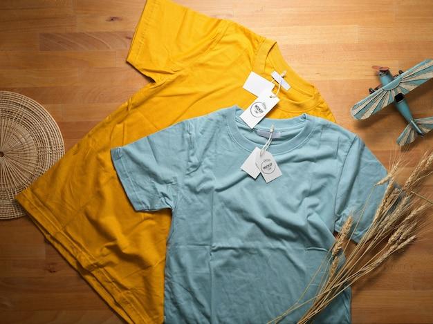 Bovenaanzicht van mock up geel en blauw t-shirt met mock up prijskaartjes op houten tafel