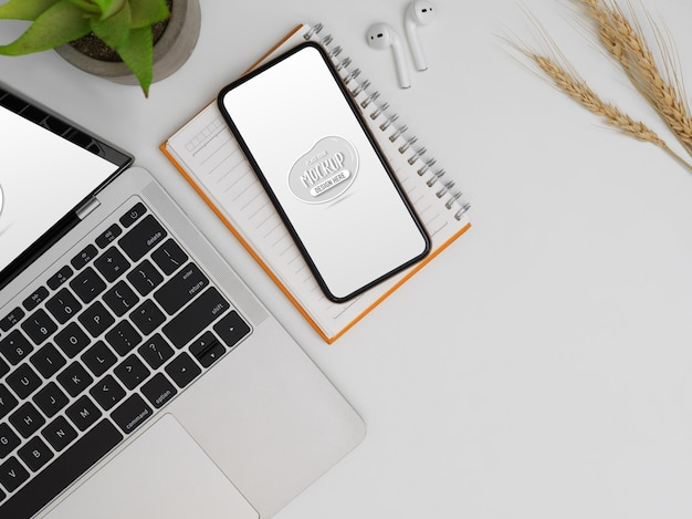 Bovenaanzicht van mock-up smartphone, laptop, notebook en kopie ruimte op wit bureau
