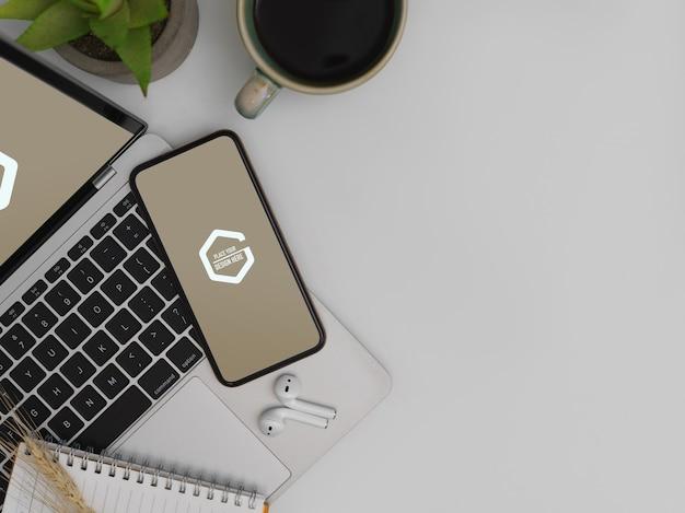 Bovenaanzicht van mock up smartphone op mock up laptop met notebook, oortelefoon