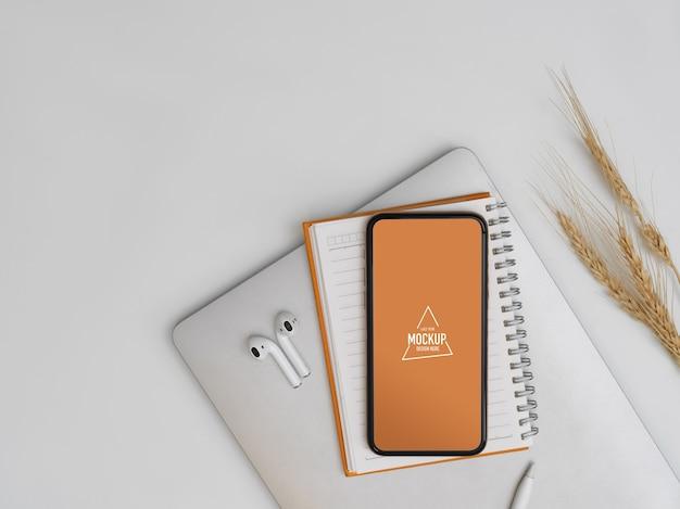 Bovenaanzicht van mock-up smartphone op notebook en laptop met oortelefoondecoratie