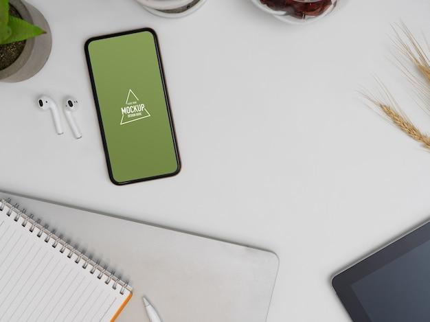 Bovenaanzicht van mock-up smartphone op werktafel met notebook, oortelefoon en benodigdheden