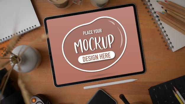 Bovenaanzicht van mockup digitale tablet met briefpapier, benodigdheden en decoraties