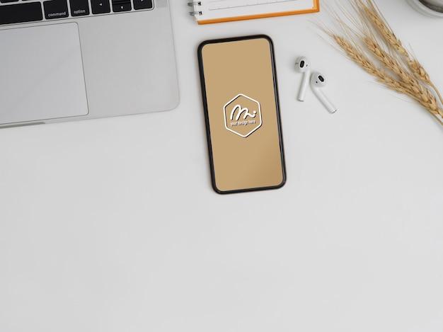 Bovenaanzicht van mockup smartphone op werktafel met laptop, oortelefoon, notebook en kopie ruimte