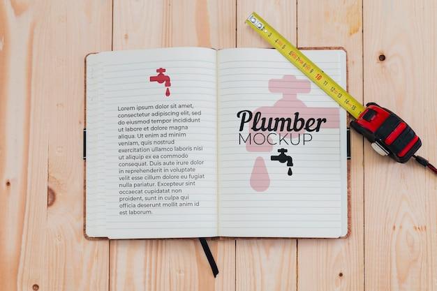 Bovenaanzicht van notebook en meetlint voor loodgieter