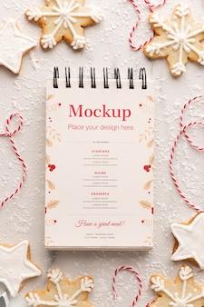 Bovenaanzicht van notebook met sneeuwvlok cookies en string