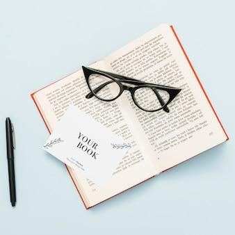 Bovenaanzicht van open boek met bril en kaart