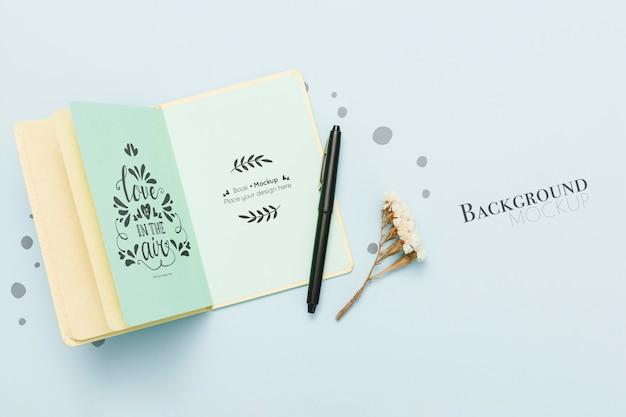 Bovenaanzicht van open boek met pen en bloemen