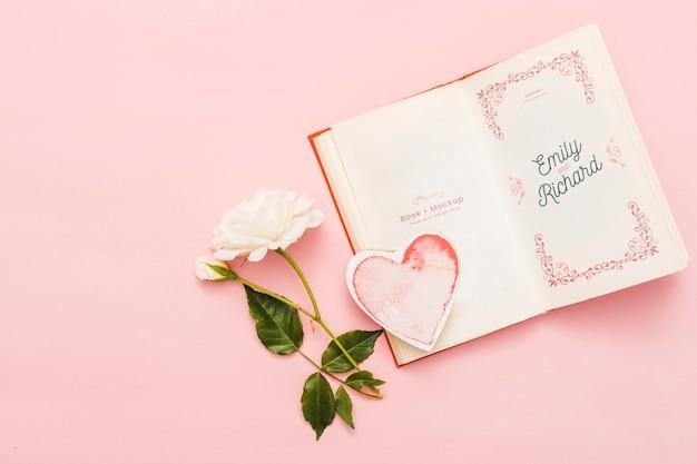 Bovenaanzicht van open boek met roos en hart