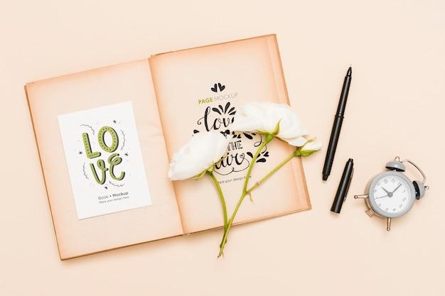 Bovenaanzicht van open boek met rozen en klok
