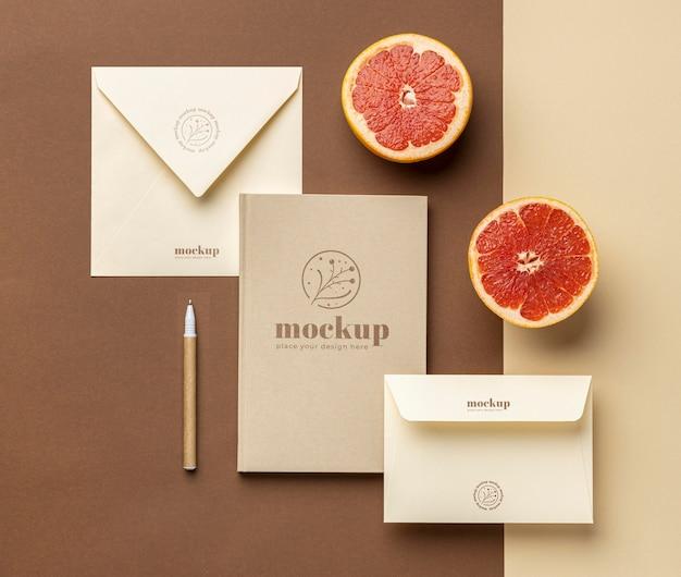Bovenaanzicht van papieren briefpapier met citrus en pen