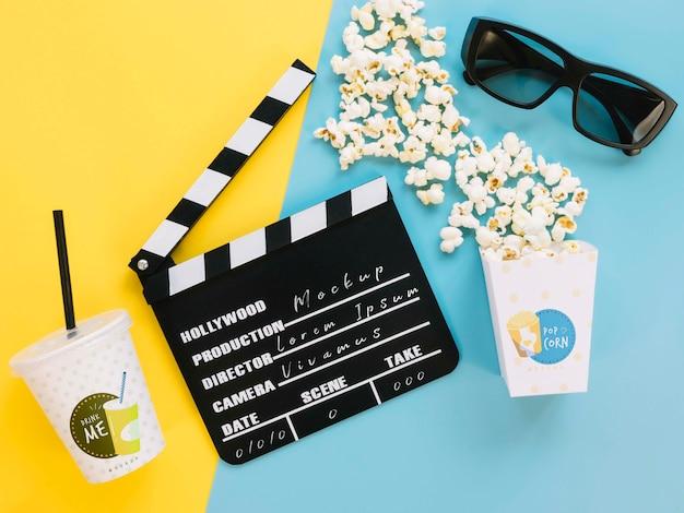 Bovenaanzicht van popcorn cup met glazen en filmklapper