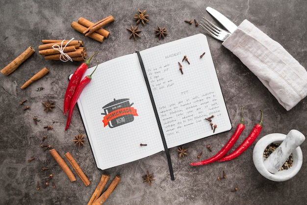 Bovenaanzicht van receptenboek met bestek en chili pepers