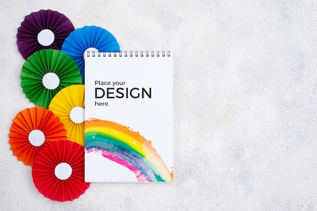 Bovenaanzicht van regenboog gekleurde rozetten en notebook