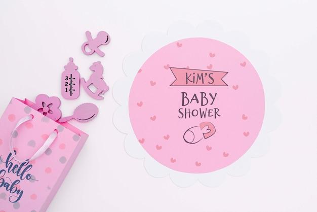 Bovenaanzicht van roze baby douche decor met geschenk tas
