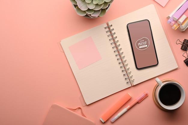 Bovenaanzicht van roze creatieve studeertafel met smartphone