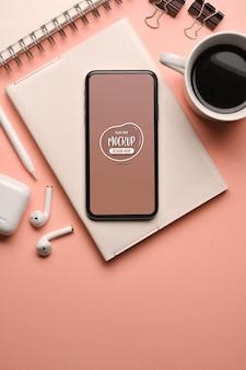 Bovenaanzicht van roze creatieve werkruimte met smartphone