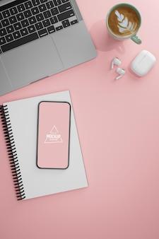 Bovenaanzicht van roze tafel met smartphone notebook laptop oortelefoon en koffiekopje 3d-rendering