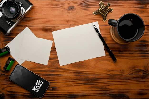 Bovenaanzicht van rustieke tafel met smartphone mockup
