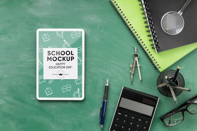 Bovenaanzicht van schoolbenodigdheden voor onderwijsdag met tablet en rekenmachine