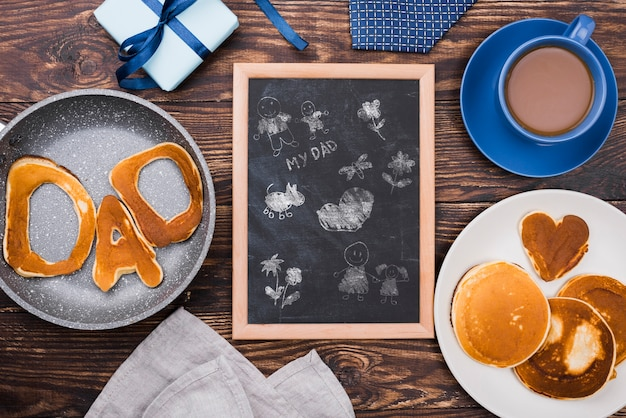 Bovenaanzicht van schoolbord met pannenkoeken en koffie voor vaderdag
