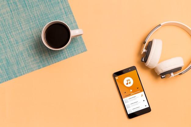 Bovenaanzicht van smartphone met koptelefoon en koffie