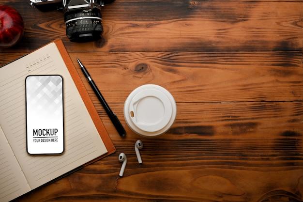 Bovenaanzicht van smartphone mockup en notebook op rustieke tafel