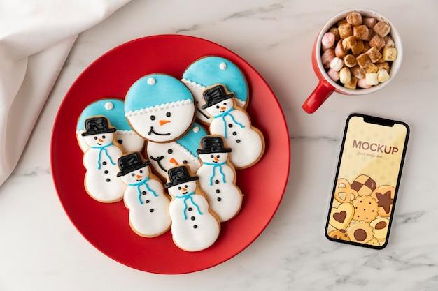 Bovenaanzicht van sneeuwpopkoekjes met mok en smartphonemodel