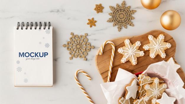 Bovenaanzicht van sneeuwvlok cookies met zuurstokken en notebook
