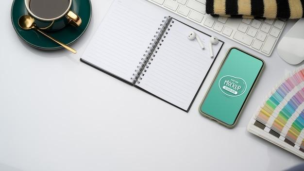 Bovenaanzicht van studie tafel met mock up smartphone, geopende notebook, elementen
