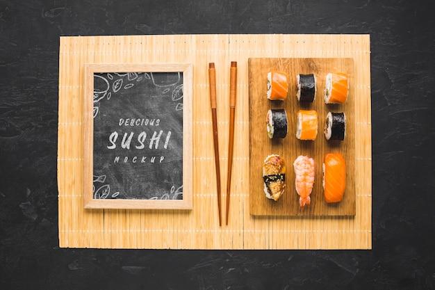 Bovenaanzicht van sushi op snijplank met stokjes en schoolbord