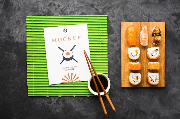 Bovenaanzicht van sushi op snijplank met stokjes en sojasaus