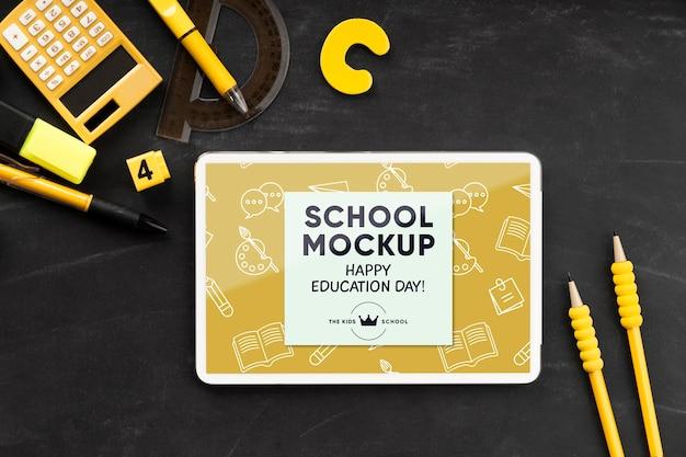 Bovenaanzicht van tablet met schoolbenodigdheden voor onderwijsdag