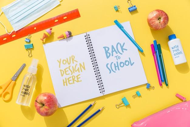 Bovenaanzicht van terug naar school notebook met potloden en appel