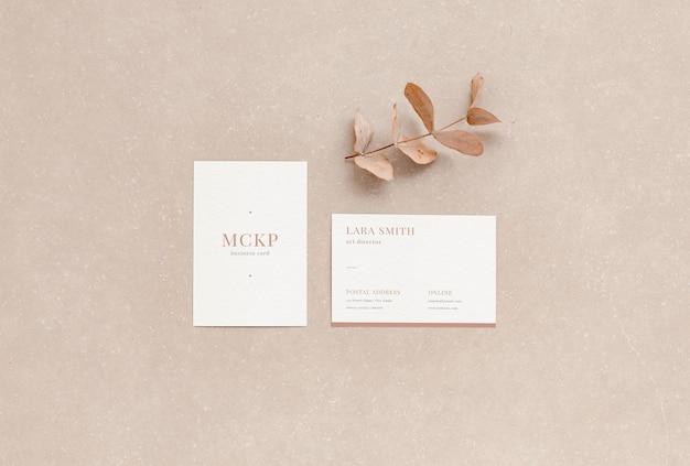 Bovenaanzicht van twee elegante visitekaartjes mockup met bladeren en natuurlijke kleuren