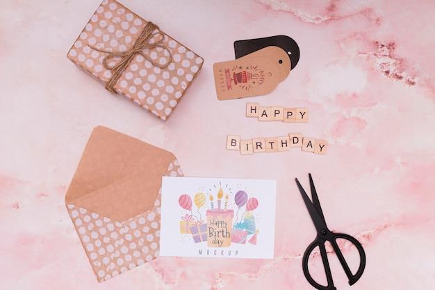 Bovenaanzicht van verjaardagscadeau met envelop en schaar
