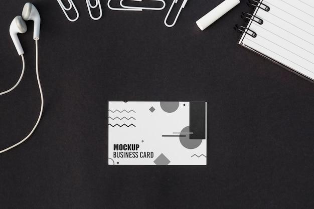 Bovenaanzicht van visitekaartje mock-up met oortelefoons en paperclips