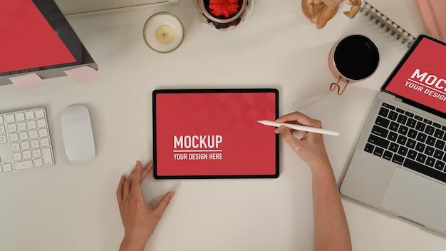 Bovenaanzicht van vrouw schrijven op leeg scherm tablet op met tafel