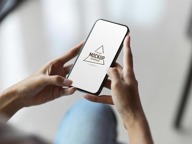 Bovenaanzicht van vrouwelijke handen met behulp van mobiele telefoon met leeg scherm en wazige achtergrond