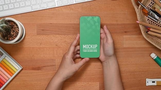 Bovenaanzicht van vrouwelijke handen met smartphonemodel