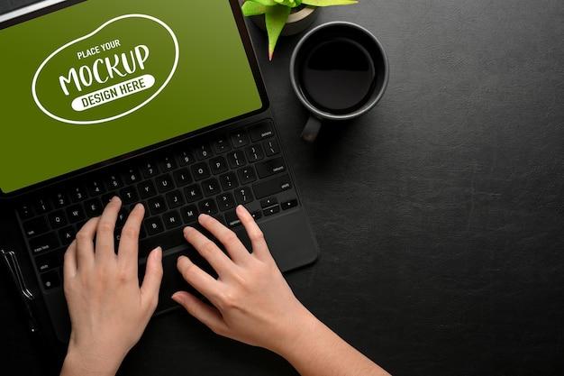 Bovenaanzicht van vrouwelijke handen typen op tablettoetsenbord op zwarte tafel met kop