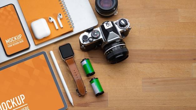 Bovenaanzicht van werkruimte met digitale apparaten, camera en accessoires