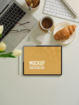 Bovenaanzicht van werkruimte met digitale tablet, ontbijtmaaltijd, leveringen