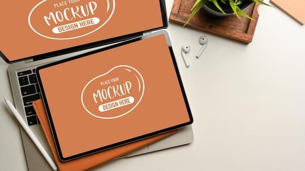 Bovenaanzicht van werkruimte met laptop en tabletmodel, briefpapier en plantpot op wit bureau