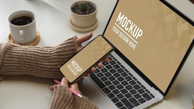 Bovenaanzicht van werkruimte met mockup voor smartphone en laptop