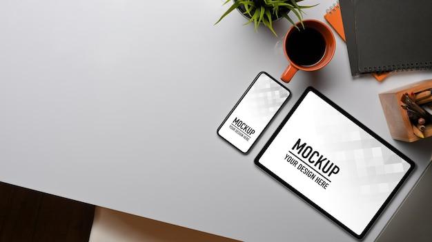 Bovenaanzicht van werkruimte met mockup voor tablet en smartphone