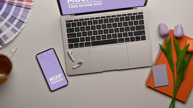 Bovenaanzicht van werkruimte met smartphone, laptopmodel en bloem versierd op tafel