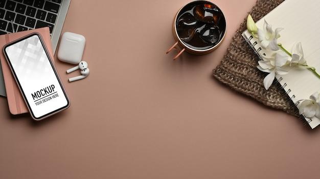 Bovenaanzicht van werkruimte met smartphonemodel, oortelefoon en briefpapier