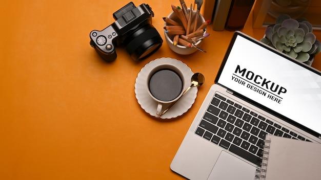 Bovenaanzicht van werktafel met laptop mockup, koffiekopje, camera, benodigdheden