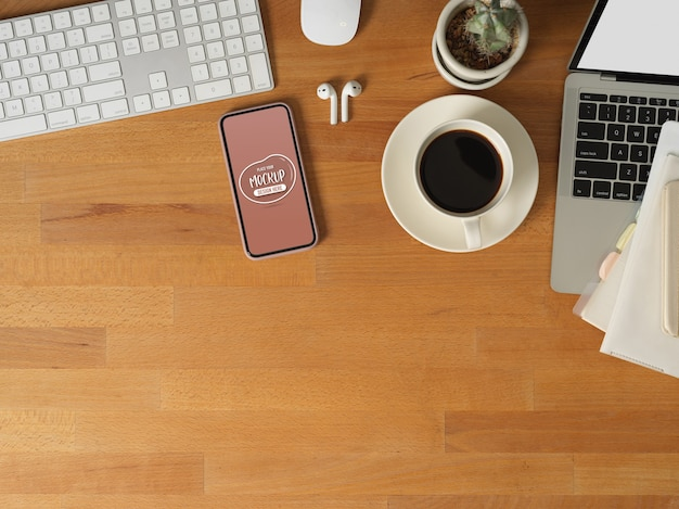 Bovenaanzicht van werktafel met mock up smartphone, laptop, computerapparaat, leveringen en kopieerruimte